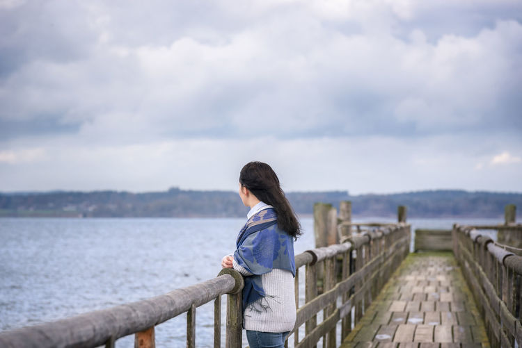 Young woman standing alone, on an old wooden bridge, thinking and gazing the horizon in the afternoon, over the Chiemsee lake, in Bavaria, Germany. Bavaria Bavarian Landscape Weather Wooden Bridge Bavarian Lakes Bridge - Man Made Structure Chiemsee Cloud - Sky Cold Temperature Early Winter Germany Nature One Person Side View Water Young Adult Young Woman
