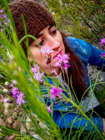 Young woman looking away by flowering plants on field