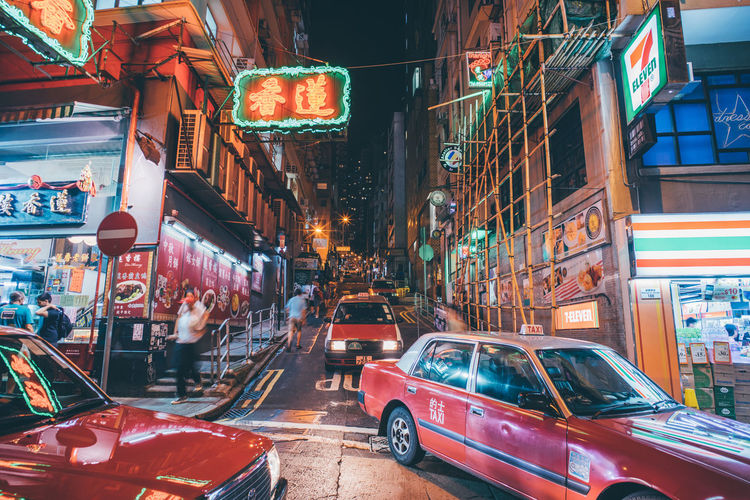 Advertisement Architecture Building Building Exterior Built Structure Car City City Life Commercial Sign Communication Illuminated Incidental People Land Vehicle Mode Of Transportation Motor Vehicle Night Road Street Text Transportation