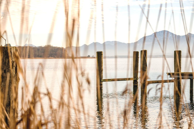 Water Mountain Tranquility No People Tranquil Scene Day Beauty In Nature Nature Reflection Waterfront Scenics - Nature Lake Sky Non-urban Scene Outdoors Wood - Material Mountain Range Built Structure Wooden Post Chiemsee Reflection Waterside