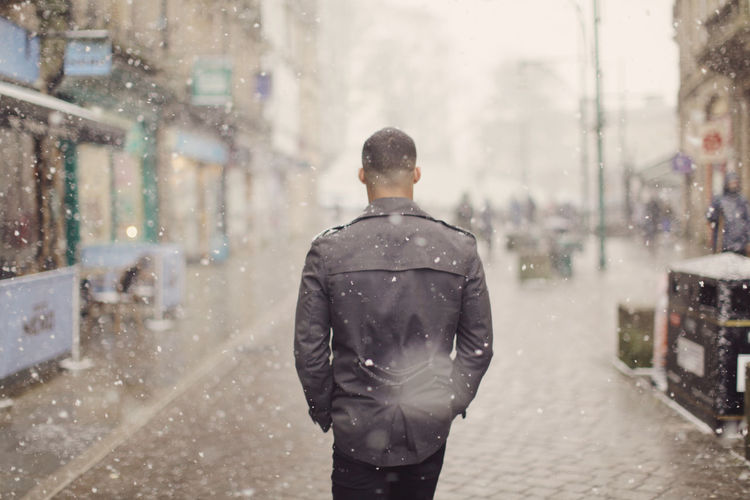 In the Snow Architecture Building Exterior City Cold Temperature Day Focus On Foreground Leisure Activity Lifestyles Men Motion One Person Outdoors Real People Rear View Road Snow Snowing Standing Street Walking Warm Clothing Weather Winter Young Adult Young Men