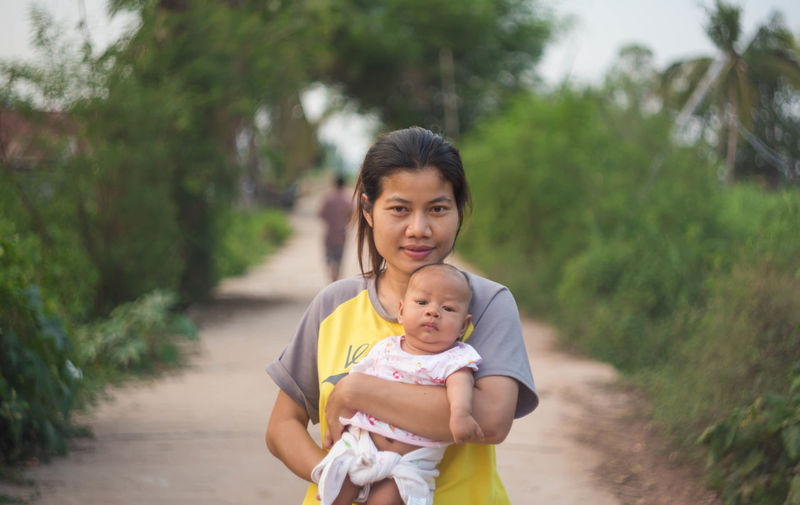 Portrait of woman carrying toddler son while standing on footpath