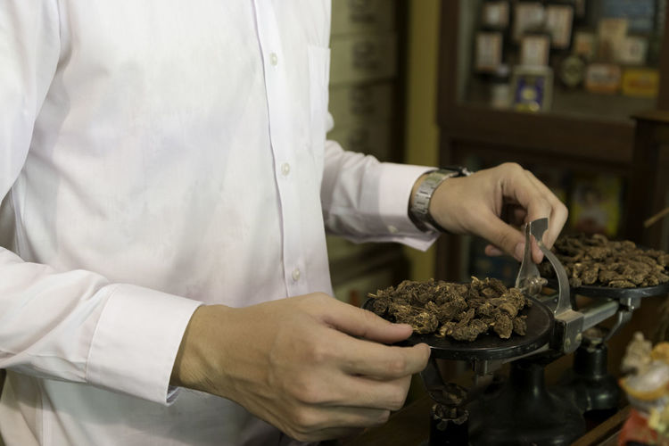 Midsection of man weighing dried food in store