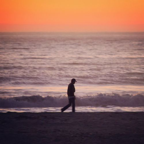 Man Walking At Beach Against Sky During Sunset