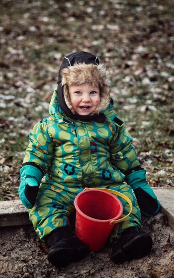 Portrait of baby boy with bucket wearing warm clothing on field