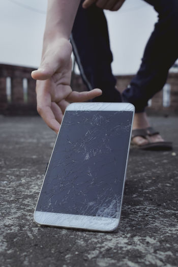Low section of man holding broken smart phone on road