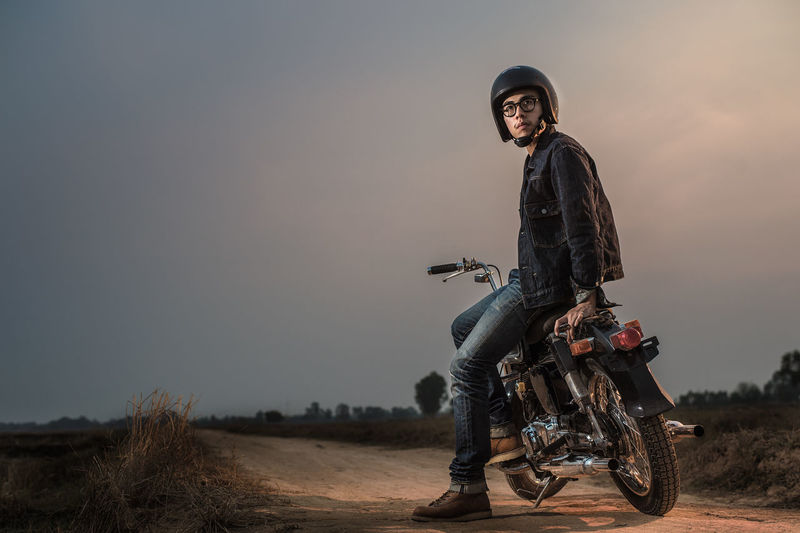 Casual Clothing Front View Full Length Helmet Land Vehicle Leisure Activity Lifestyles Looking At Camera Mode Of Transportation Motorcycle Nature One Person Outdoors Real People Ride Riding Sky Standing Transportation Young Adult