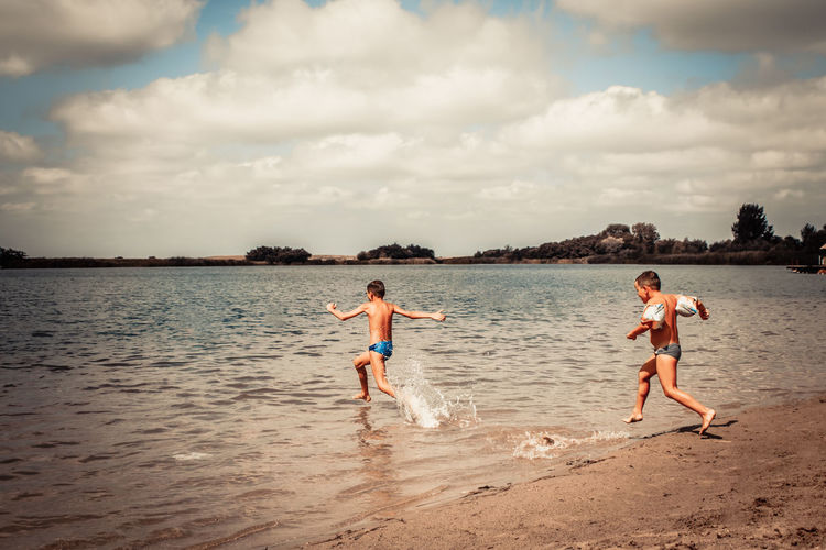 Carefree boys running in the water and having fun on the beach in summer day,