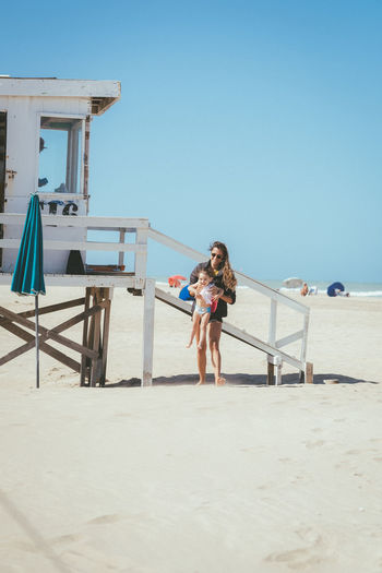 Full length of mother carrying girl standing at beach against clear sky