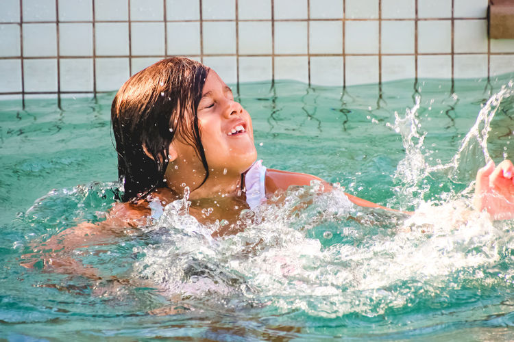 young girl having fun in the pool splashing water Water Swimming Pool Pool Lifestyles Enjoyment Swimming Child Leisure Activity Splashing Real People One Person Fun Motion Happiness Childhood Nature Portrait Headshot Outdoors Turquoise Colored Girls Vacations