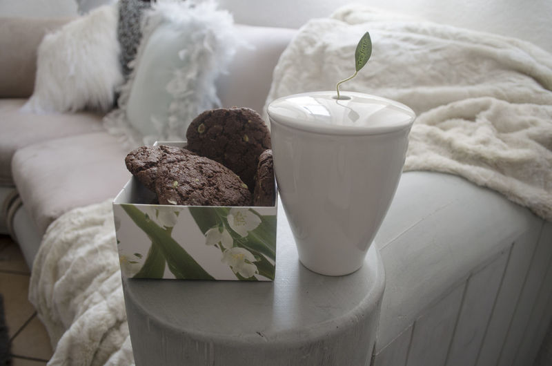 Close-up of cookies in box by container on sofa