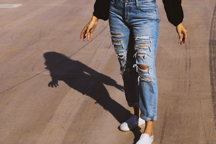 Low section of woman wearing jeans standing on road