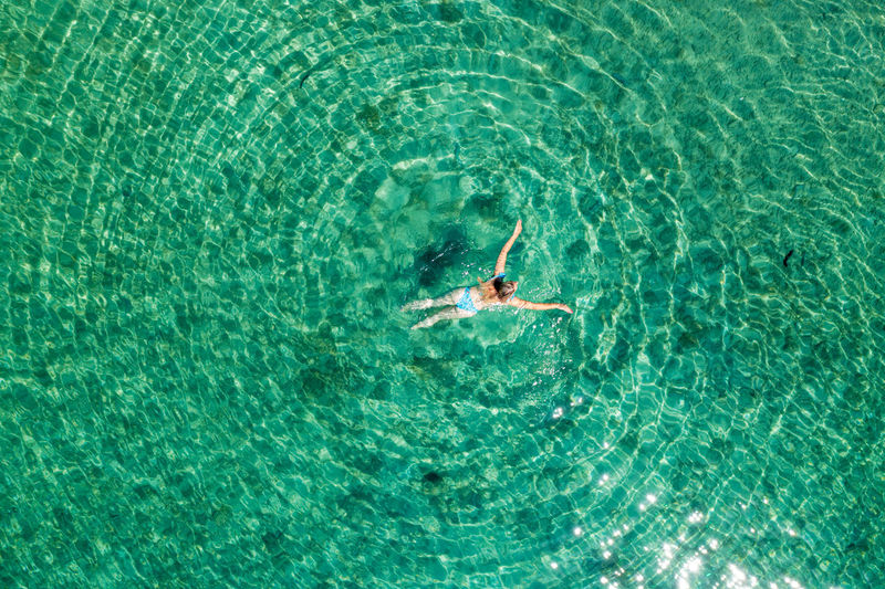 Aerial view of a girl floating in the turquoise sea on the cres island, adriatic sea, croatia