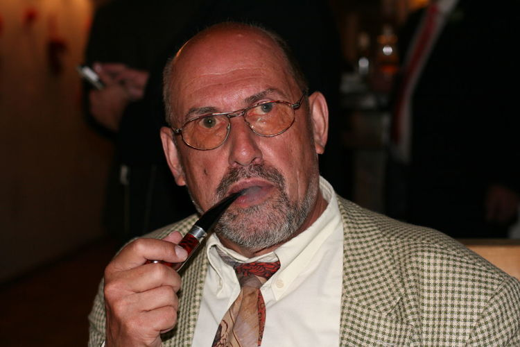 Close-Up Of Senior Man Smoking With Pipe While Sitting Indoors