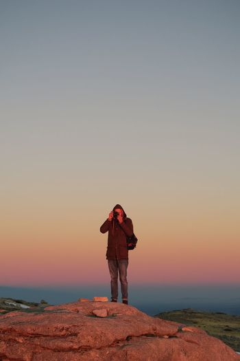 Full length of man photographing through camera while standing on rock during sunset