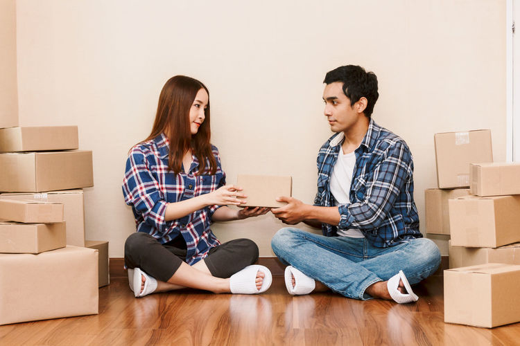 Young couple with cardboard box at home - Business online and delivery concept Adult Box Box - Container Boyfriend Cardboard Cardboard Box Change Couple - Relationship Flooring Heterosexual Couple Home Ownership Indoors  Men Moving House Packing Relocation Sitting Togetherness Two People Women Wood Young Adult Young Couple Young Men Young Women