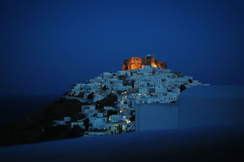 Castle and buildings against blue sky at night