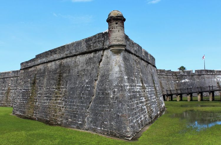 Fortress Wall and Mote, Castillo de San Marcos Augustine FL Castillo De San Marcos Historical Sights St Augustine, FL Architecture Blue Building Exterior Built Structure Clear Sky Day Florida History Fort Fortress Grass Historical Historical Fort History Nature No People Old Outdoors The Past Tourism Travel Travel Destinations Water Historic Building Historic Exterior Old Ruin Fortified Wall