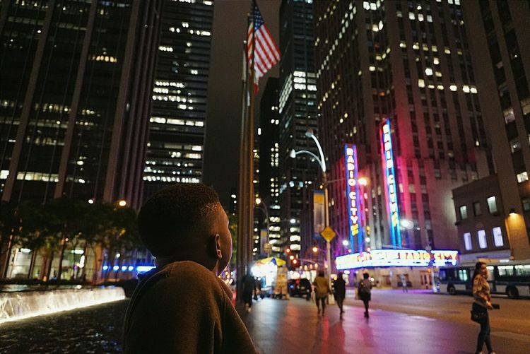 Man Looking At Illuminated Buildings In City