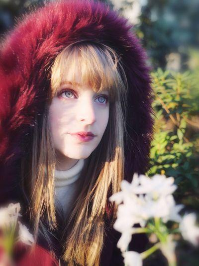 Beautiful young woman in fur coat looking away
