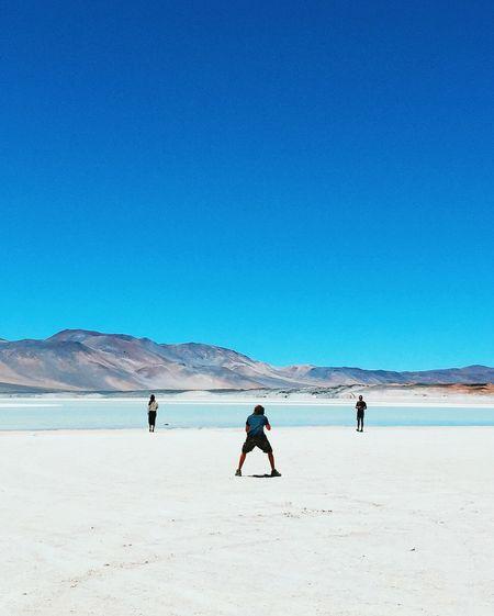 TOURISTS WALKING ON BEACH