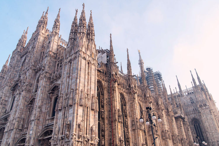 Milan Duomo Cathedral facade, marble carvings Low Angle View Building Exterior Place Of Worship Religion Built Structure Architecture Belief Spirituality Sky The Past History Building Travel Destinations Day City Nature Gothic Style Outdoors No People Spire  Duomo Milan Italy
