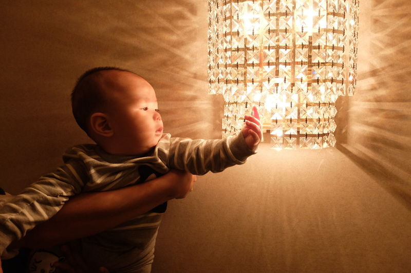Close-up of cute boy touching chandelier