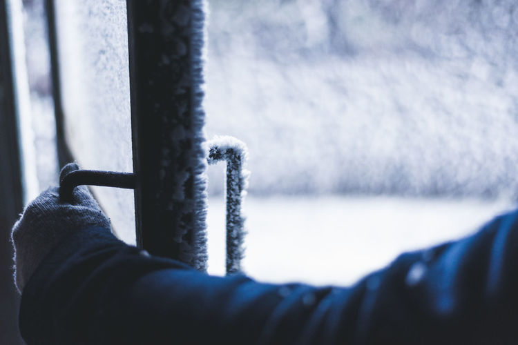 Cropped image of hand holding frozen door