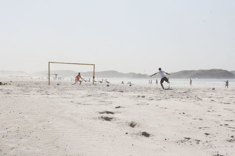Male friends playing soccer at beach against clear sky