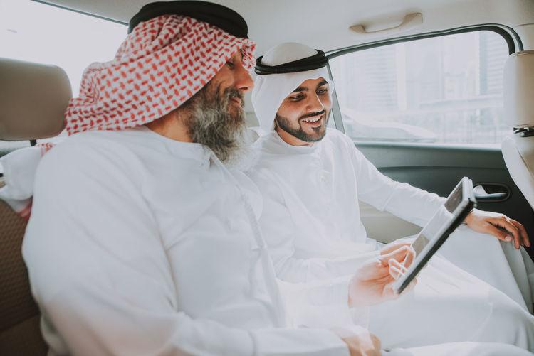 Men wearing dish dash traveling in car