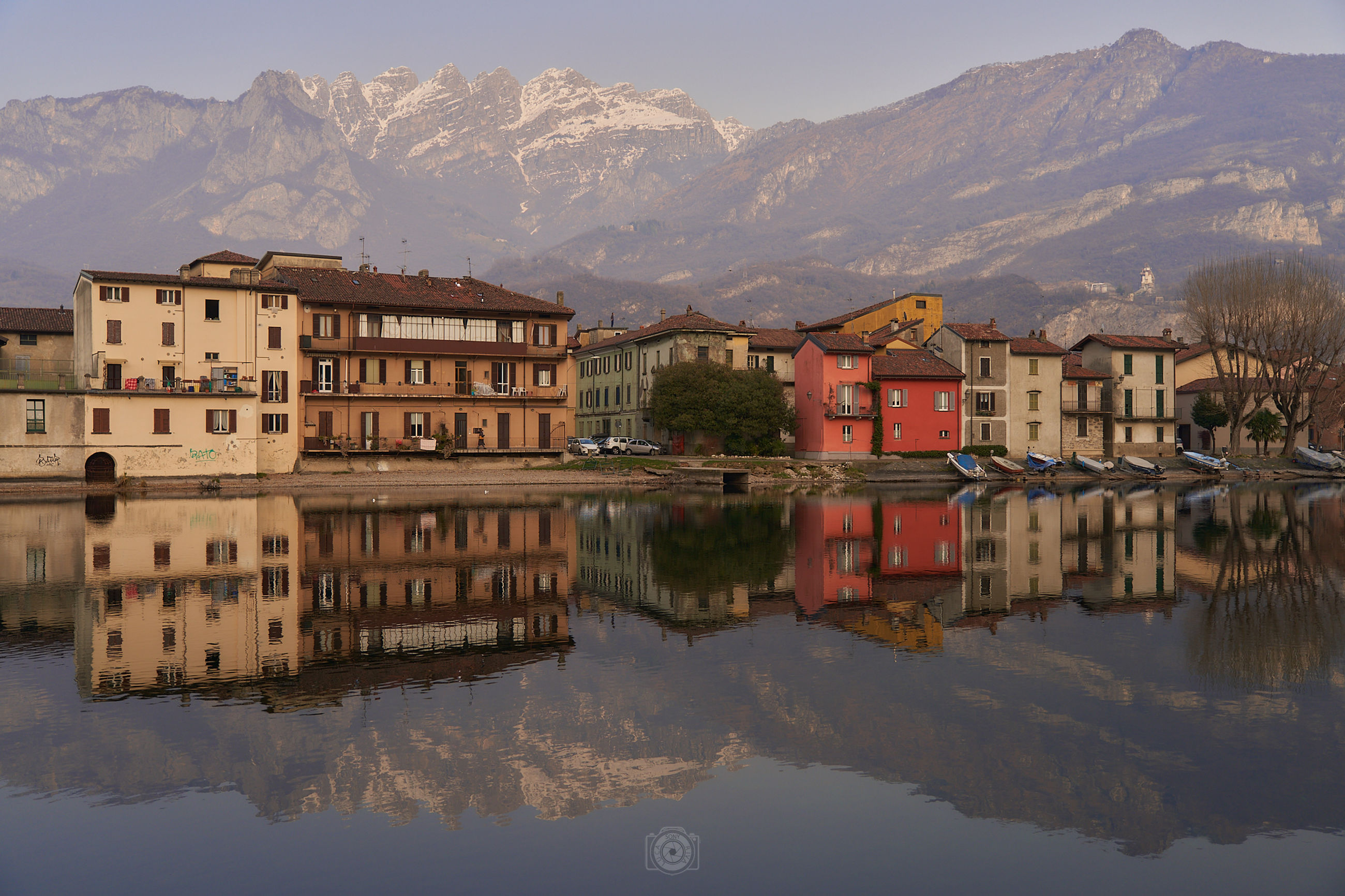 reflection, water, architecture, mountain, building exterior, building, built structure, lake, nature, house, mountain range, sky, city, town, travel destinations, scenics - nature, landscape, morning, residential district, no people, environment, travel, beauty in nature, tourism, waterfront, outdoors, reflection lake, history, cityscape, land, tranquility, snow, religion