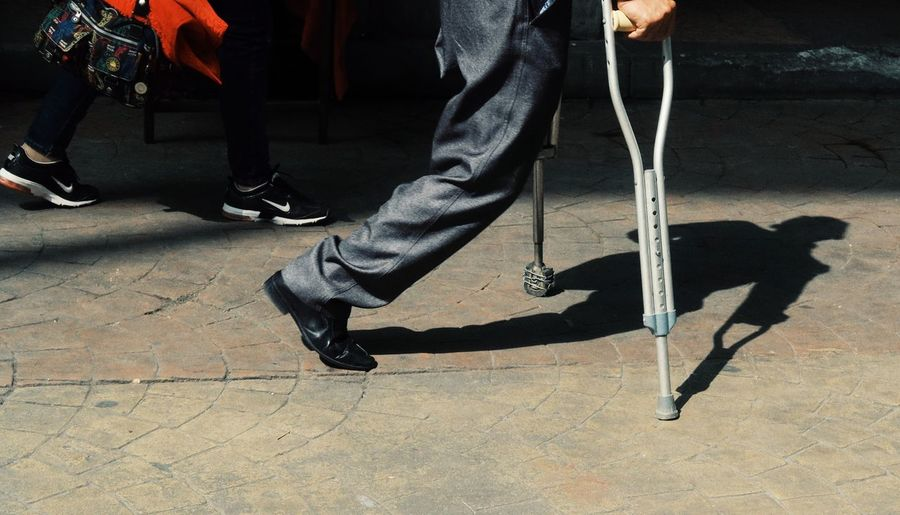 Low section of disabled man walking with help of canes on footpath