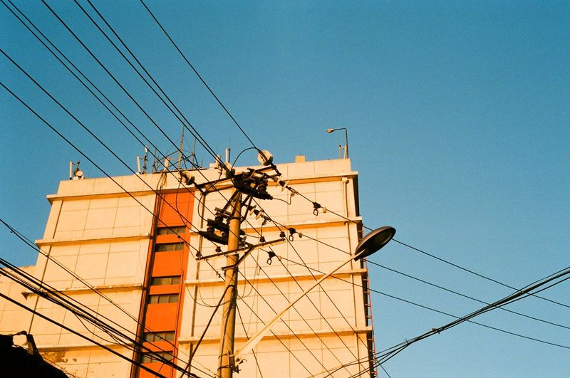 Low angle view of electricity pylon against building against clear blue sky
