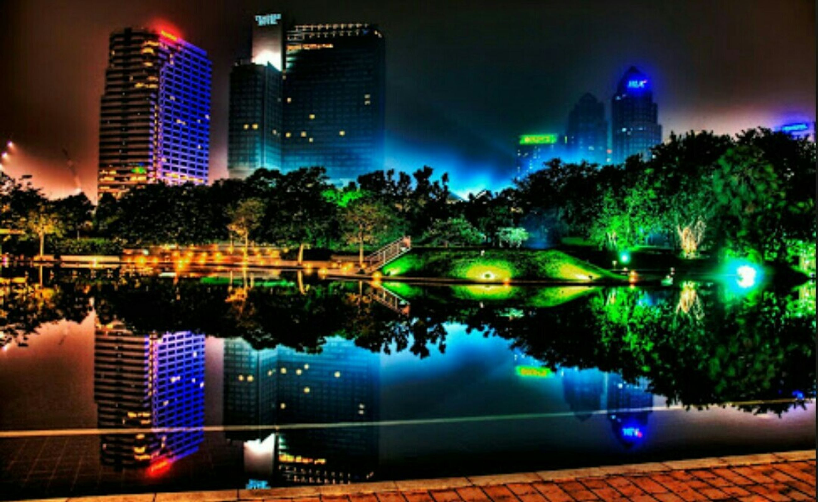 building exterior, architecture, illuminated, built structure, night, city, skyscraper, modern, cityscape, tall - high, tower, tree, office building, sky, reflection, financial district, water, urban skyline, city life, building