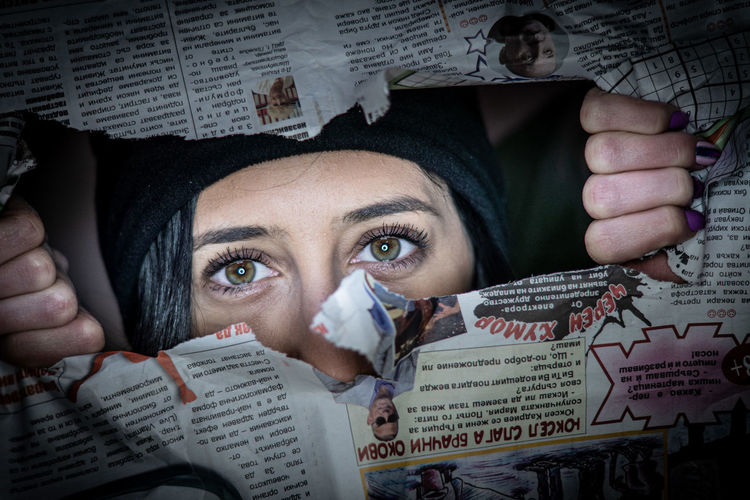 Portrait of young woman tearing paper