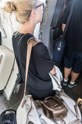 Side view of mid adult woman standing in airplane