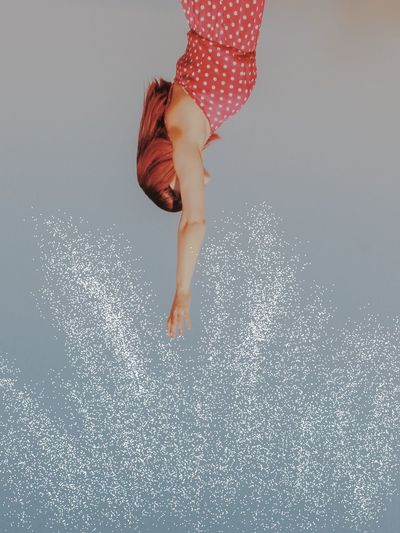 Low section of woman walking on water against gray background