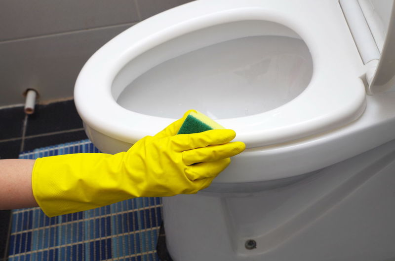 Cropped Hand Cleaning Toilet In Bathroom