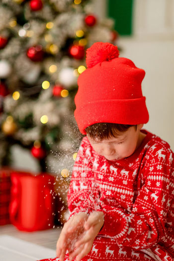 Midsection of boy looking at christmas tree