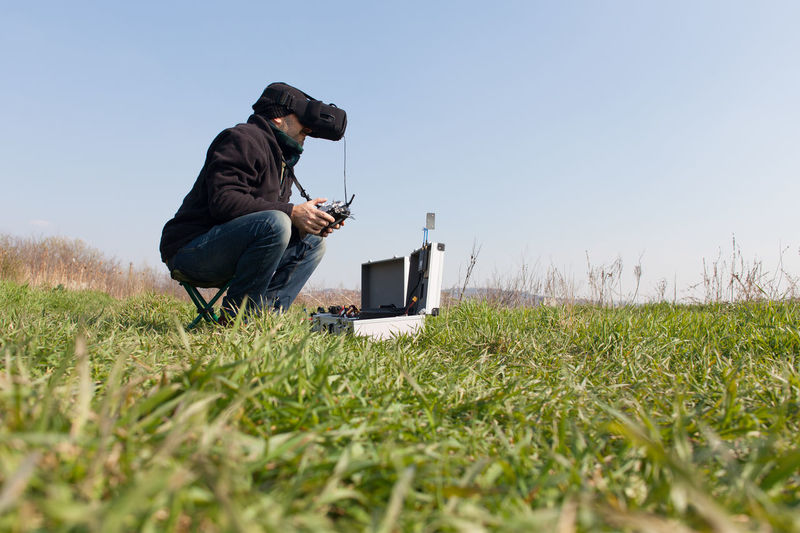 Man using virtual reality simulator while holding drone remote control on grassy field