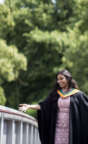 Smiling young woman wearing graduation gown standing against trees