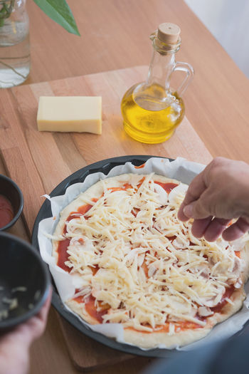 Close-up of person making pizza