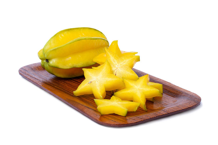 Star fruit and slice of star fruit on the wooden rounded rectangle tray isolated on white background Eating Food And Drink Isolated Nature Raw Tray Carambola Close-up Cut Out Food Food And Drink Freshness Fruit Gourmet Healthy Eating Object Organic Ripe Shape SLICE Starfruit Vegetable White Background Wood - Material Yellow