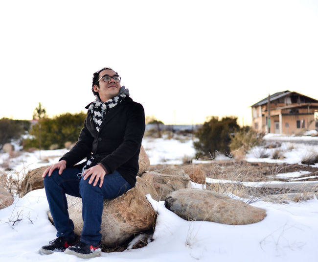 Man sitting on snow against sky