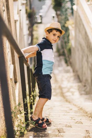 Portrait of cute boy wearing hat standing on steps