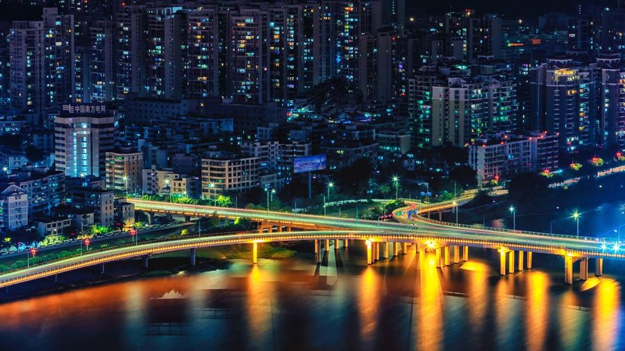 Illuminated bridge and buildings in city at night