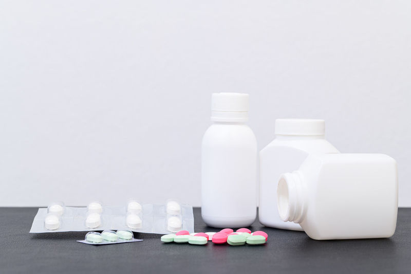 Close-up of bottles on table against white background