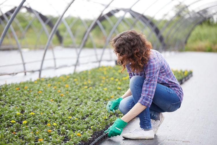 Smiling woman working in botanical garden