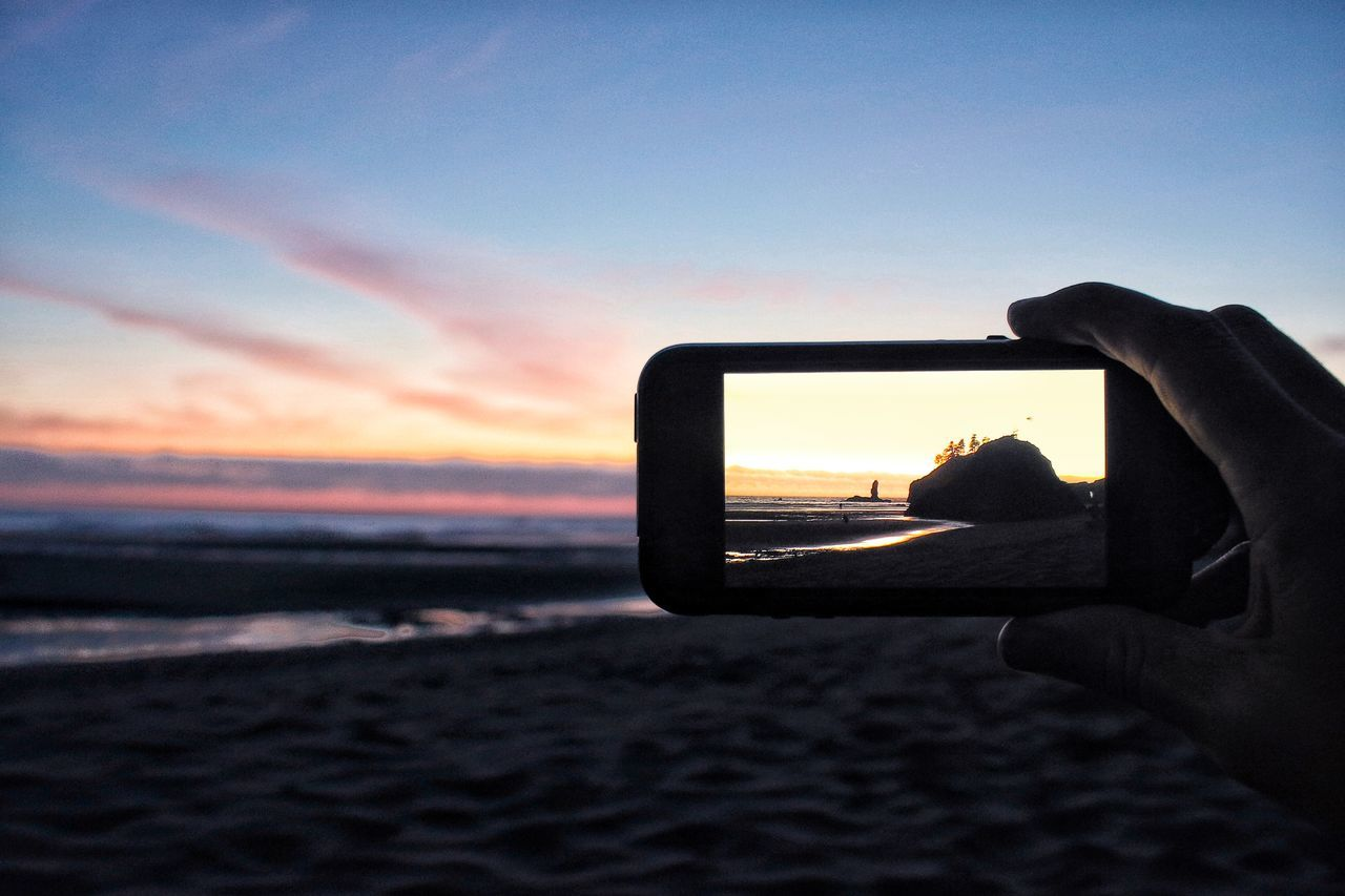 Cropped hand photographing at beach using smart phone during sunset