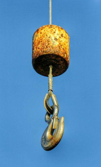 Rusty hook of crane against clear blue sky
